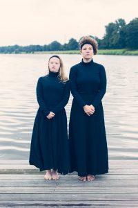 zwei Frauen stehen in schwarzen Kleidern, an einem See, nebeneinander