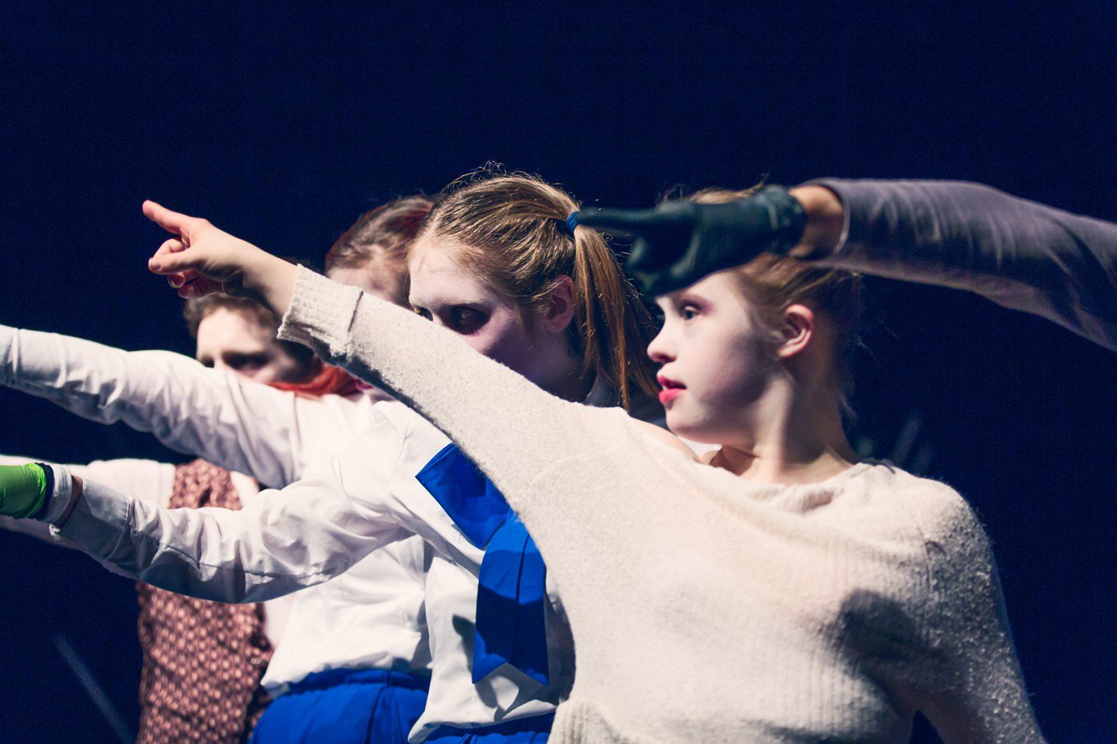 eine Reihe von TänzerInnen zeigt in eine Richtung
