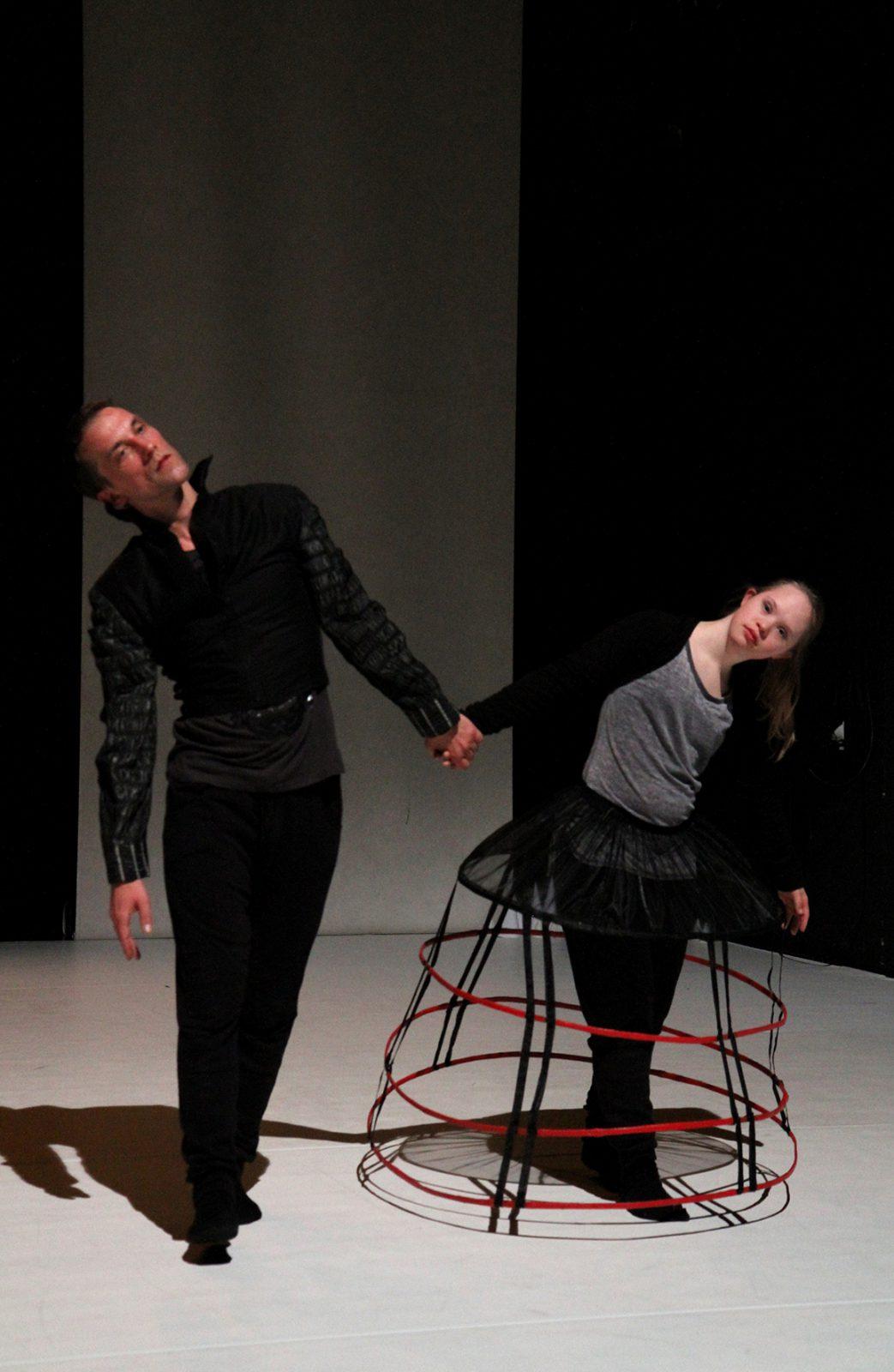 zwei Tänzerinnen Hand in Hand, beugen sich voneinander weg