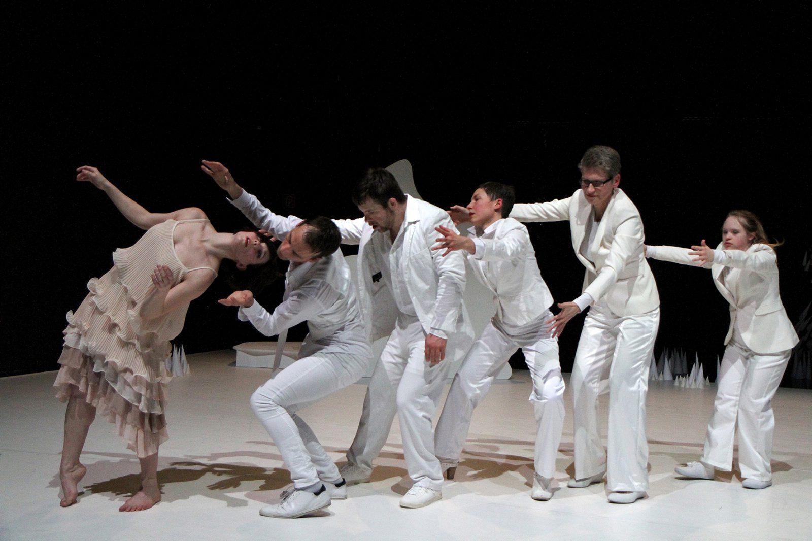 TänzerInnen in weißen Kostümen in einer Reihe strecken die Arme aus zu einer anderen Tänzerin