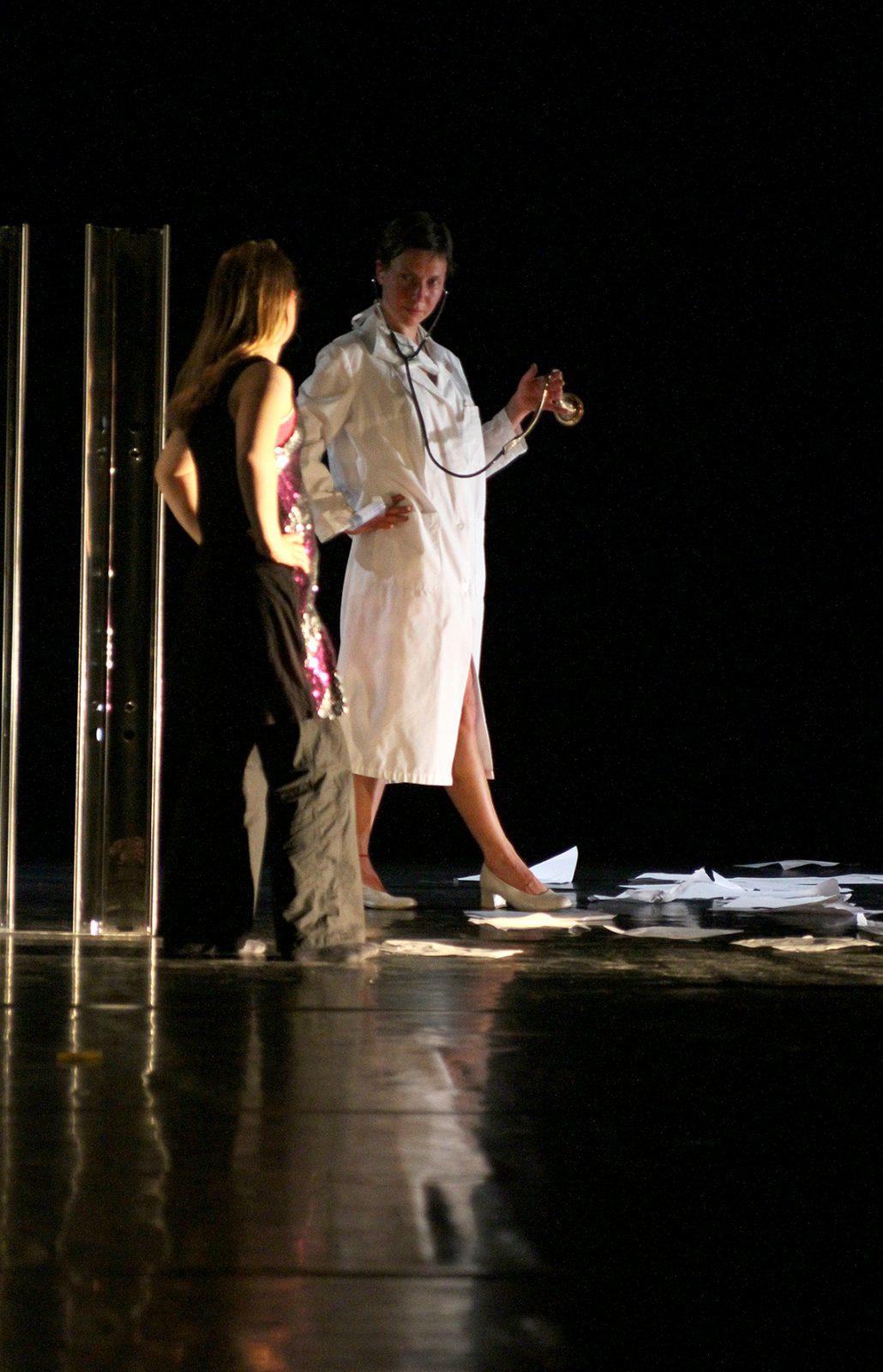 zwei Tänzerinnen gehen in eine Richtung, eine trägt einen Arztkittel