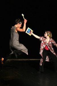 eine Tänzerin mit einer Bürste in der Hand springt vor einer anderen Tänzerin hoch