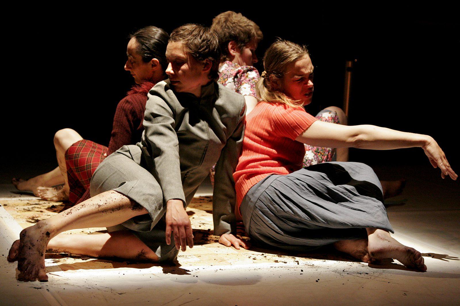 vier Tänzerinnen sitzen am Boden mit Erde