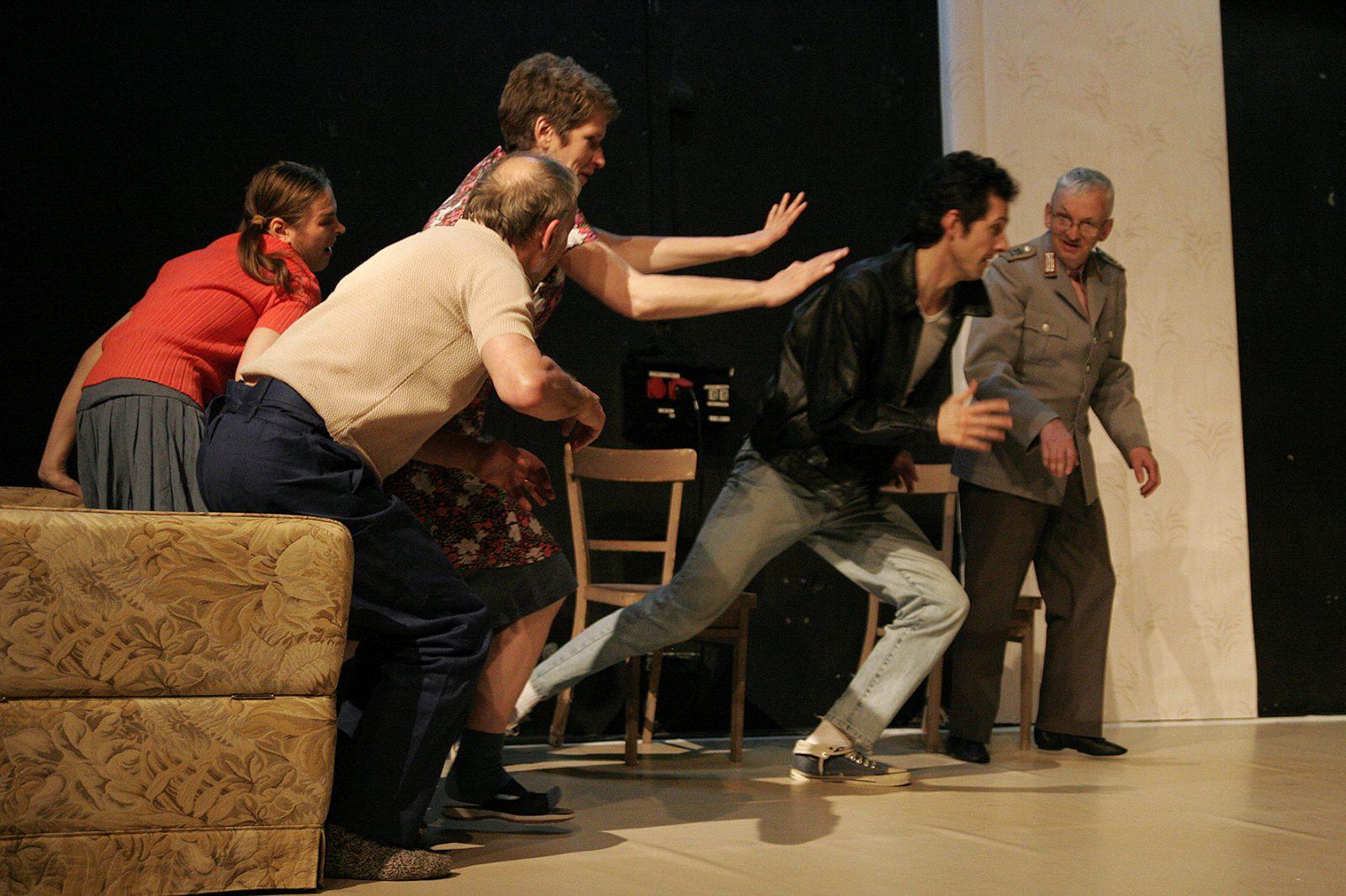 eine Gruppe von TänzerInnen rennt von einem Sofa weg