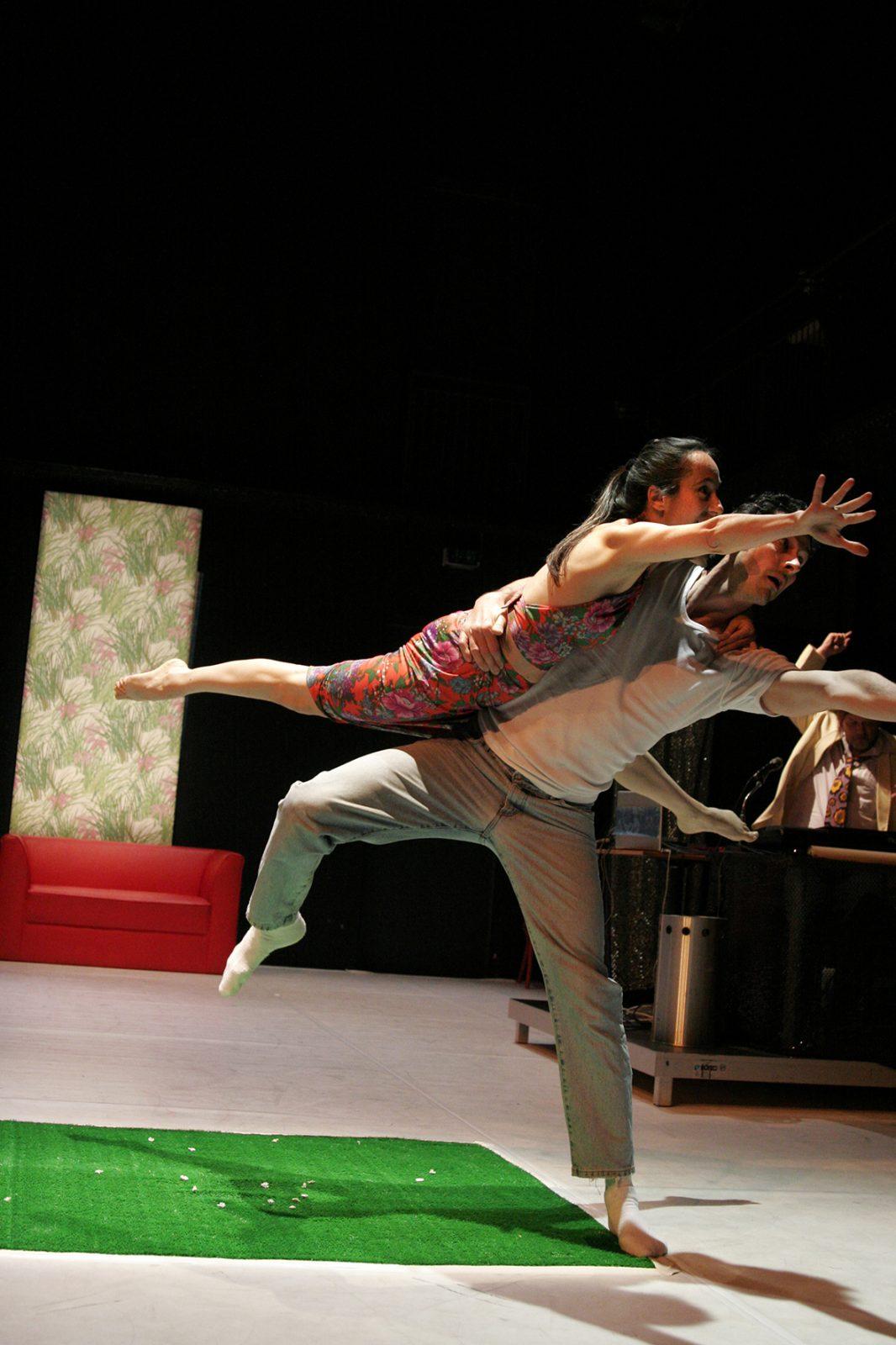 eine Tänzerin liegt auf der Hüfte eines Tänzers der auf einem Bein steht