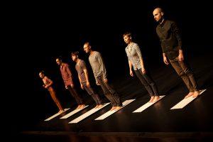 Bühnenaufnahme. Eine Gruppe von sechs Personen steht in einer Reihe auf unterschiedlich langen, flachen weissen Brettern.