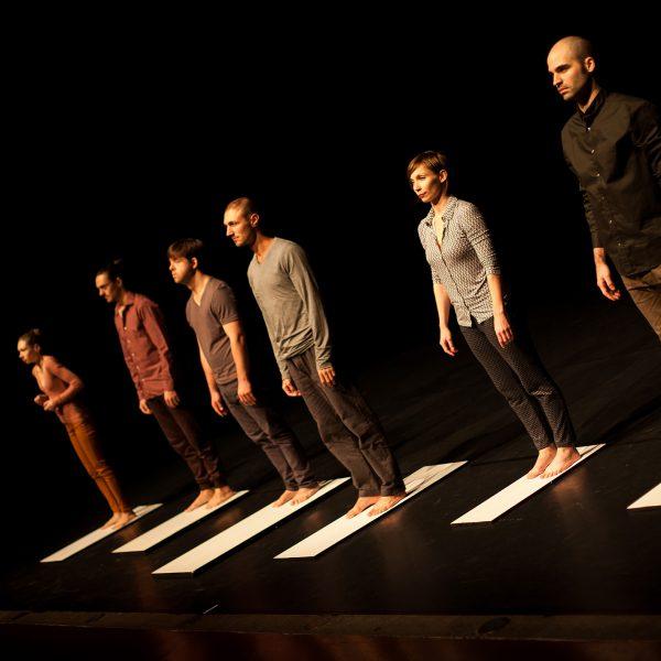 sechs DarstellerInnen stehen auf weißen Brettern