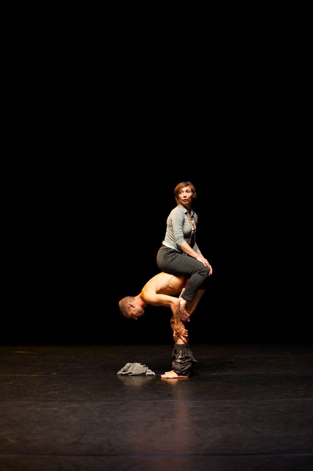 eine Frau sitzt auf dem Rücken eines Tänzers, der steht und sich dabei auszieht.