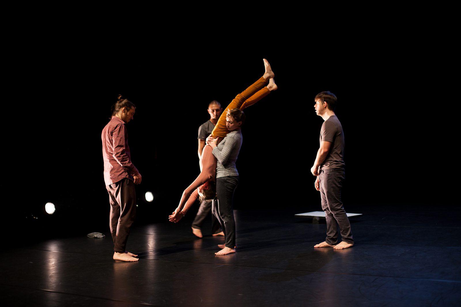 eine Tänzerin hebt eine andere Tänzerin Kopfüber. Frei Tänzer schauen ihr zu.