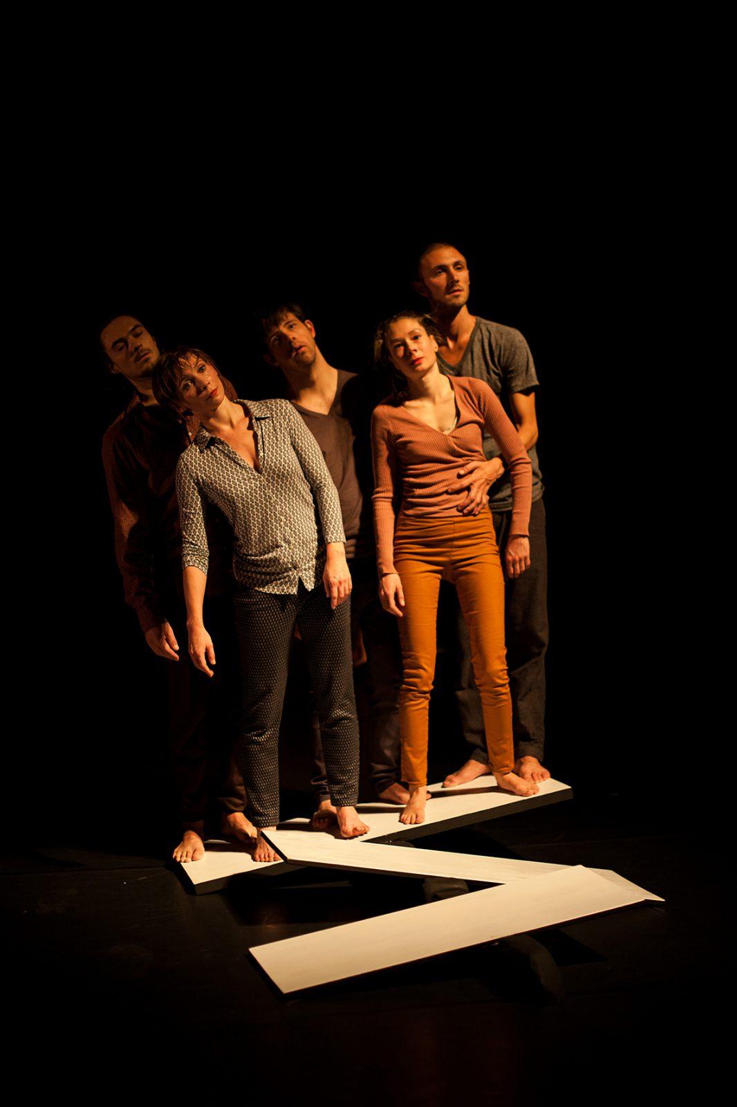 Fünf Tänzer stehen zur Seite geneigt auf einem Kippbrett
