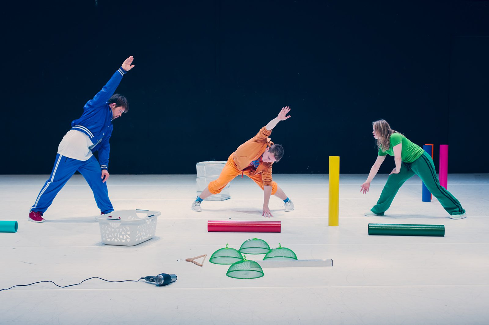 drei TänzerInnen mit Dingen am Boden