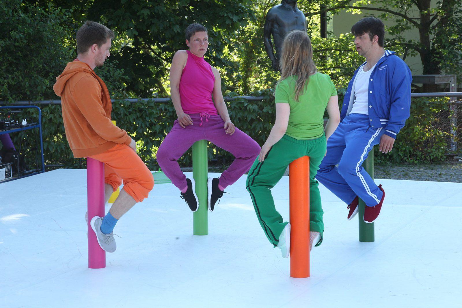 vier TänzerInnen sitzen auf aufgestellten Rohren gegenüber