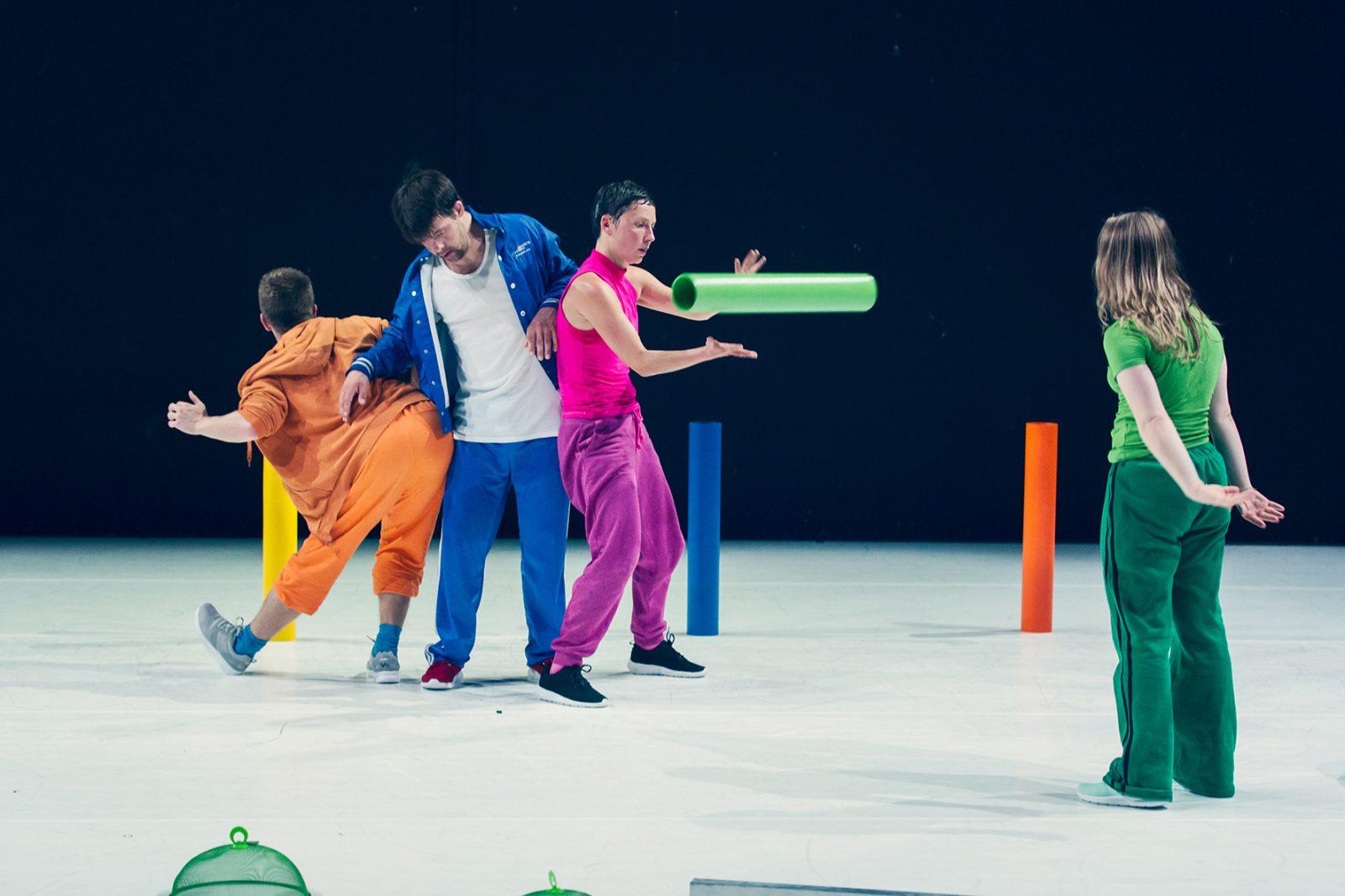 vier TänzerInnen in vier Farben mit Rohren