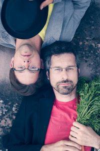 zwei Männer liegen auf dem Boden, einer mit Hut, der andere mit Karotten in der Hand