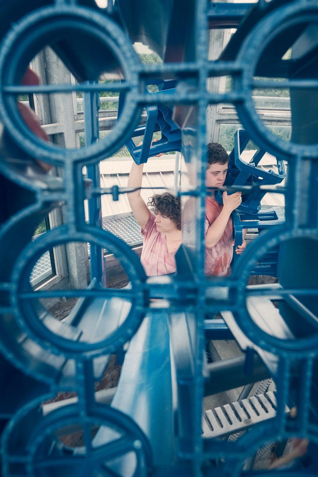 zwei TänzerInnen mit blauen Getränkekisten