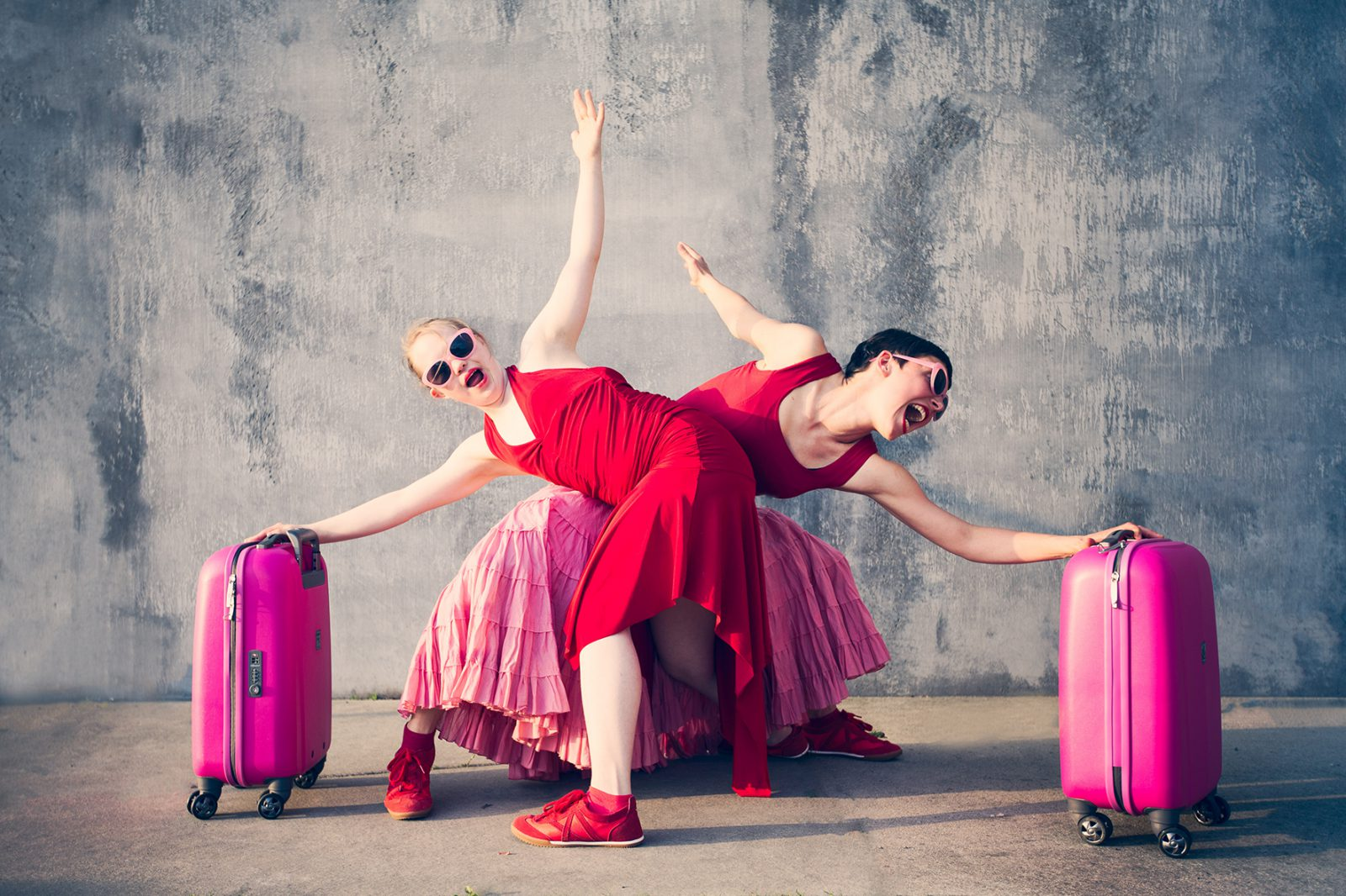 zwei Tänzerinnen gegenüber, mit rosa Koffern