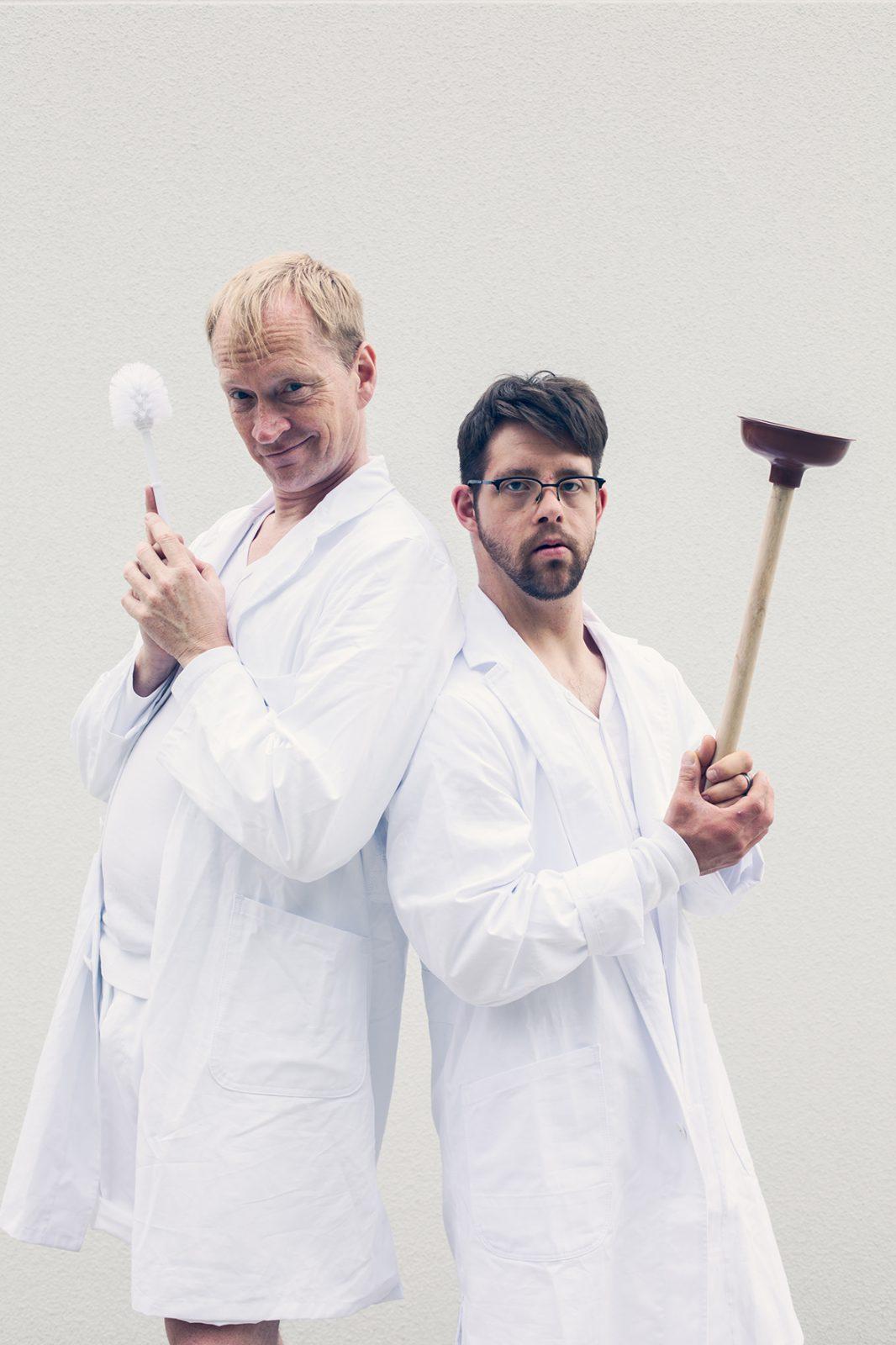 zwei Darsteller stehen mit einer Bürste und einem Pömpel nebeneinander