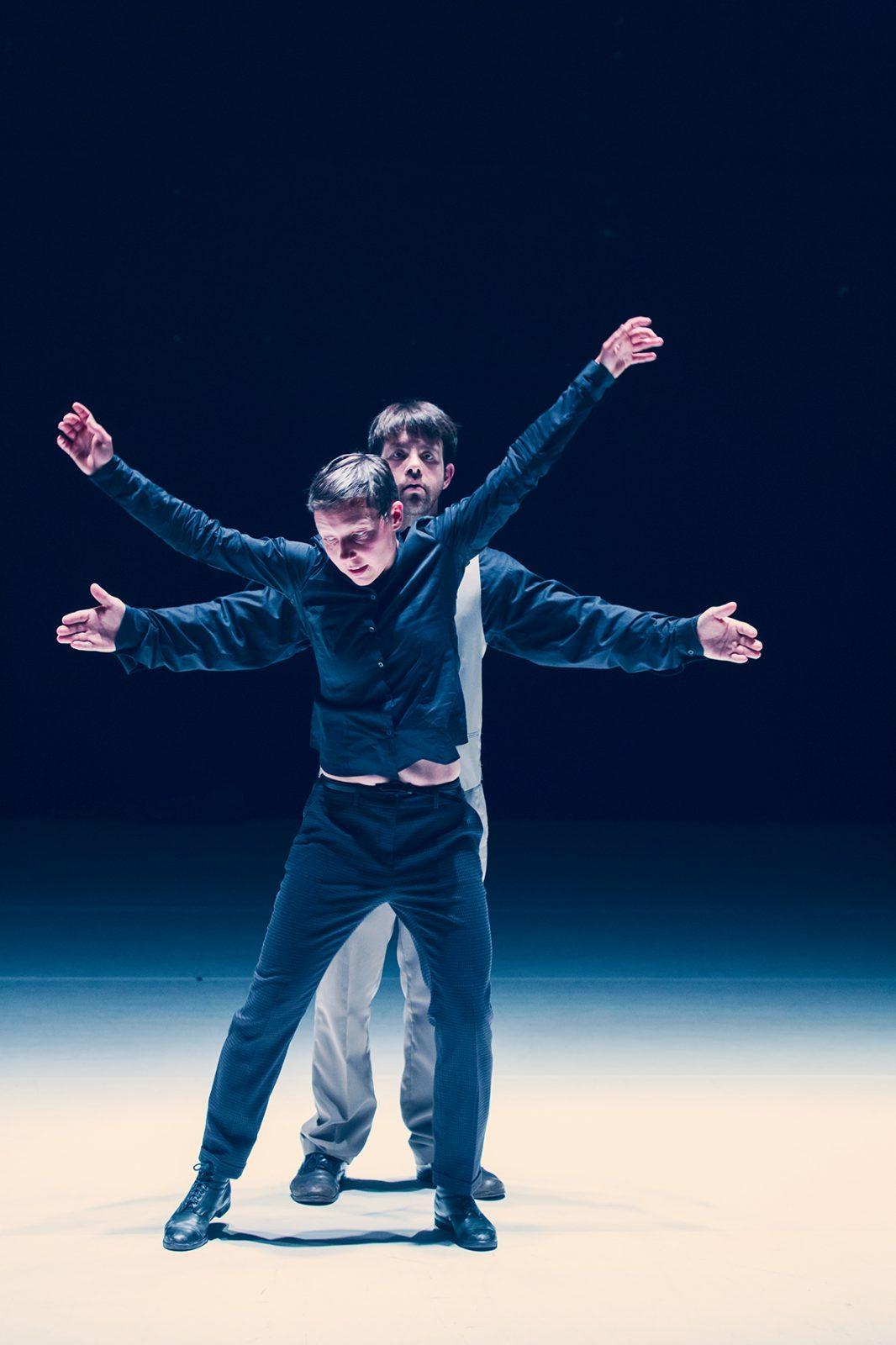 ein Tänzer steht hinter einer Tänzerin mit den Armen zur Seite
