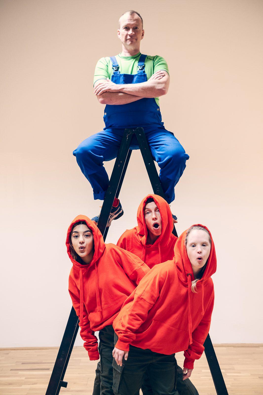 Mann auf einer Leiter, Tänzerinnen davor