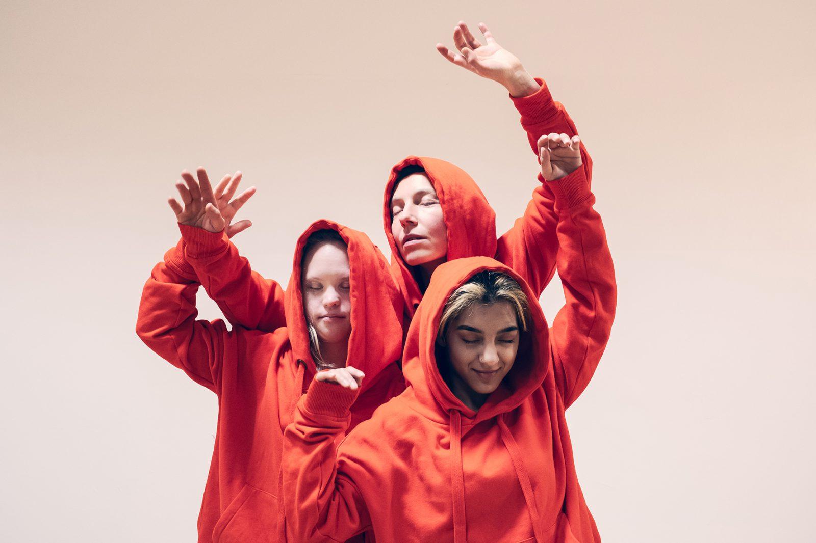 Drei Tänzerinnen in orangen Kaputzenpullis