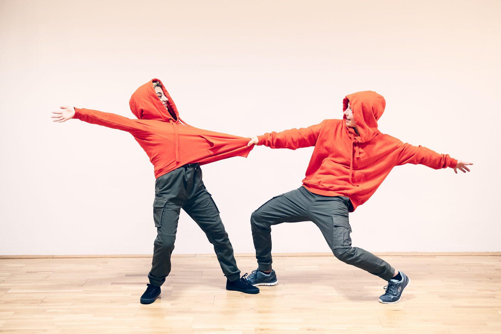 zwei Tänzerinnen ziehen an Kaputzenpullis