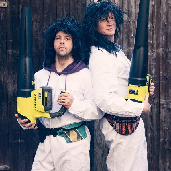 Zwei Männer mit Laubbläser und Perücken stehen nebeneinander. Es geht los.