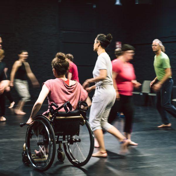 eine Gruppe von Menschen läuft durcheinander, in der Mitte eine Rollstuhlfahrerin