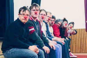 eine Gruppe von Menschen mit roten Nasen sitzt nebeneinander