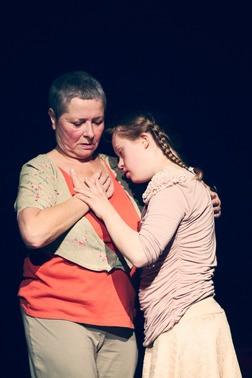 Frau mit der Hand in der eigenen Brust. Eine jüngere Frau steht neben ihr.