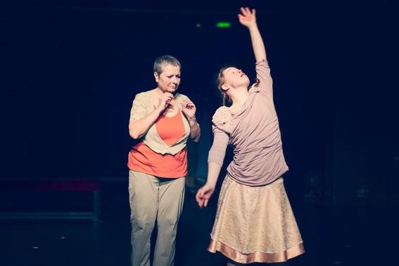 Frau mit erhobenem Arm, neben einer anderen Frau, die ängstlich aussieht