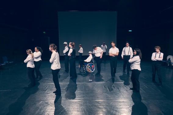 Gruppe junger Menschen in einer Bühne und nach links schauend