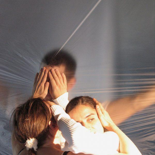 drei TänzerInnen mit Händen am Kopf in Folie