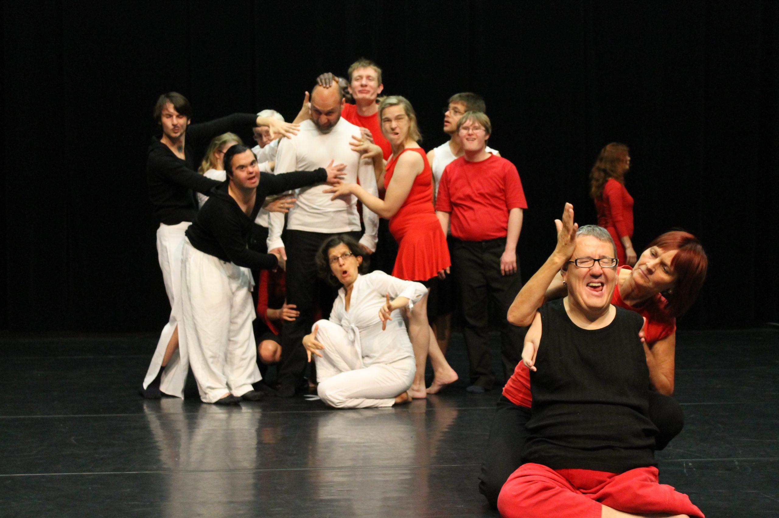 eine Gruppe von Tänzerinnen fasst einen Tänzer an, ein Tänzer ohne Arme wird von einer Tänzerin berührt