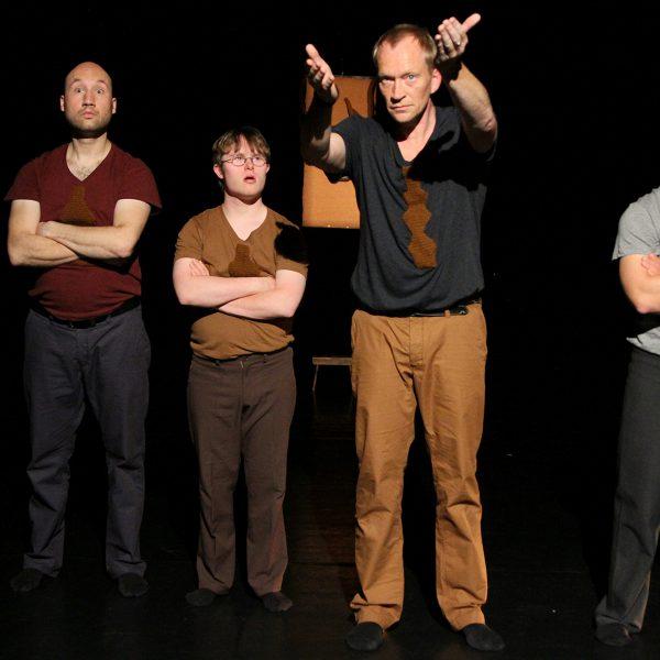 vier Männer mit verschränkten Armen, einer streckt sie aus