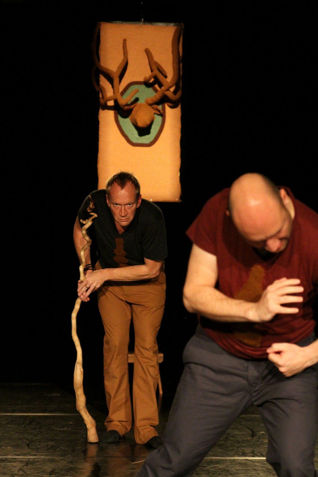 ein Mann mit einem Stock hinter einem anderen Tänzer