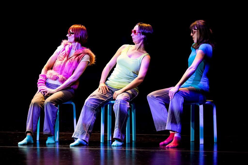 Drei Frauen sitzen nebeneinander auf Hockern