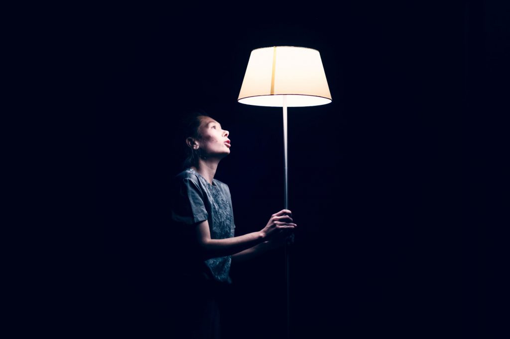 Frau hält eine Lampe hoch