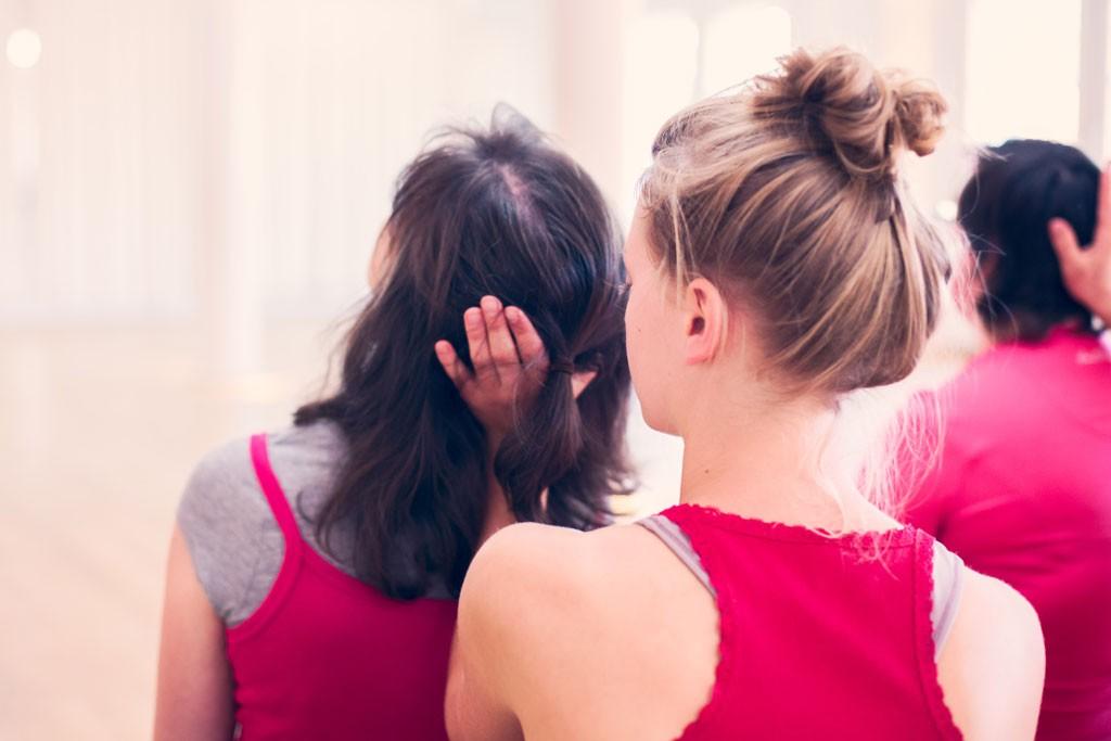 eine Tänzerin hält den Hinterkopf einer anderen Tänzerin