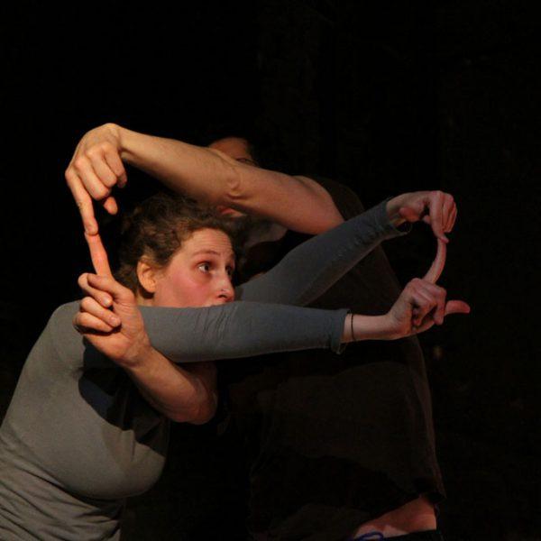 zwei TänzerInnen kreuzen die Arme und berühren ihre Finger
