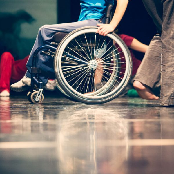 eine Rollstuhlfahrerin in einer Gruppe von TänzerInnen