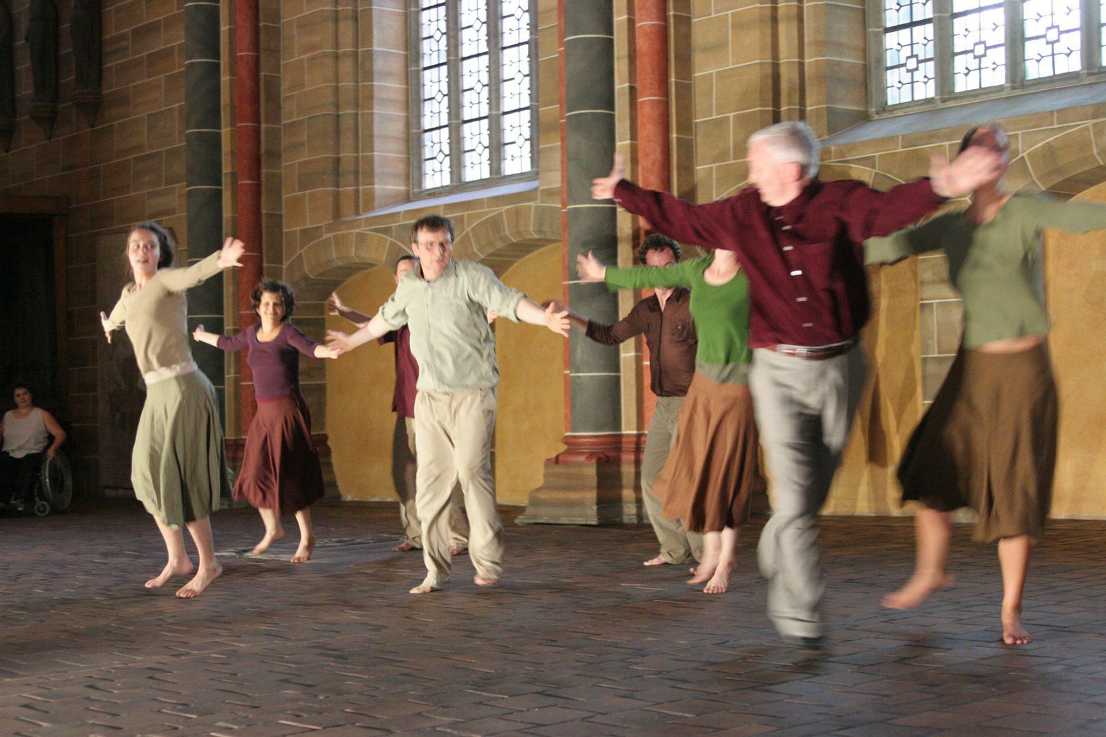 eine Gruppe im Dom zu Bremen mit Armen zur Seite