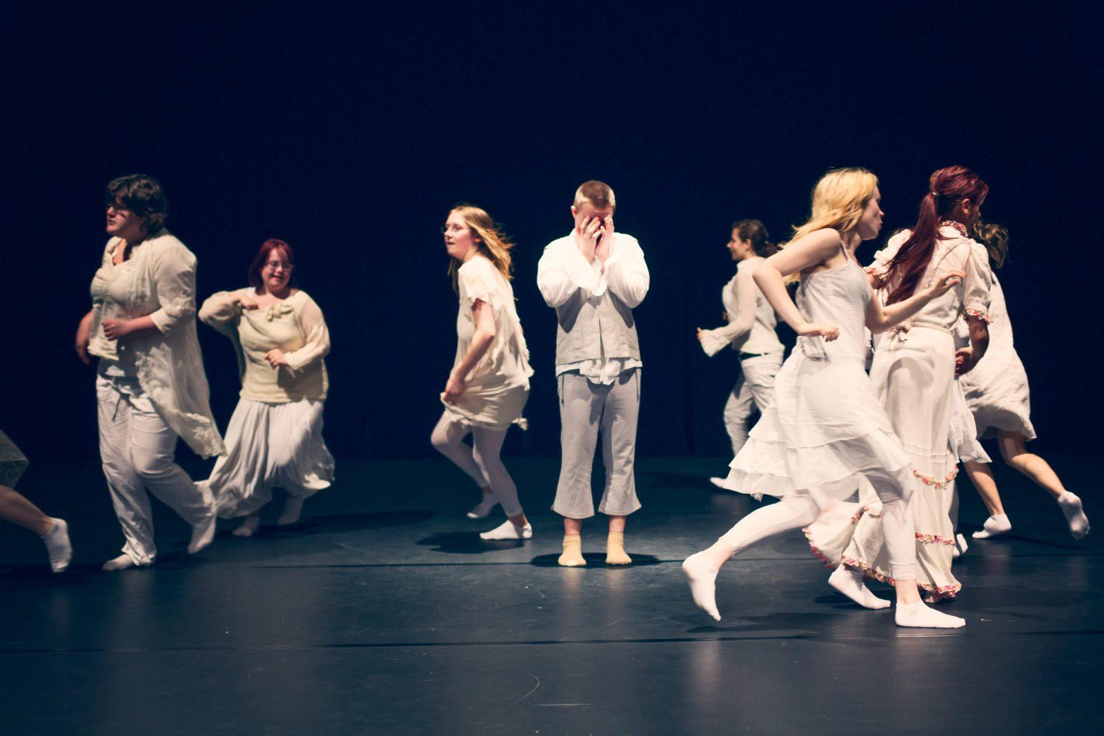eine Gruppe von Tänzerinnen läuft um einen Tänzer herum