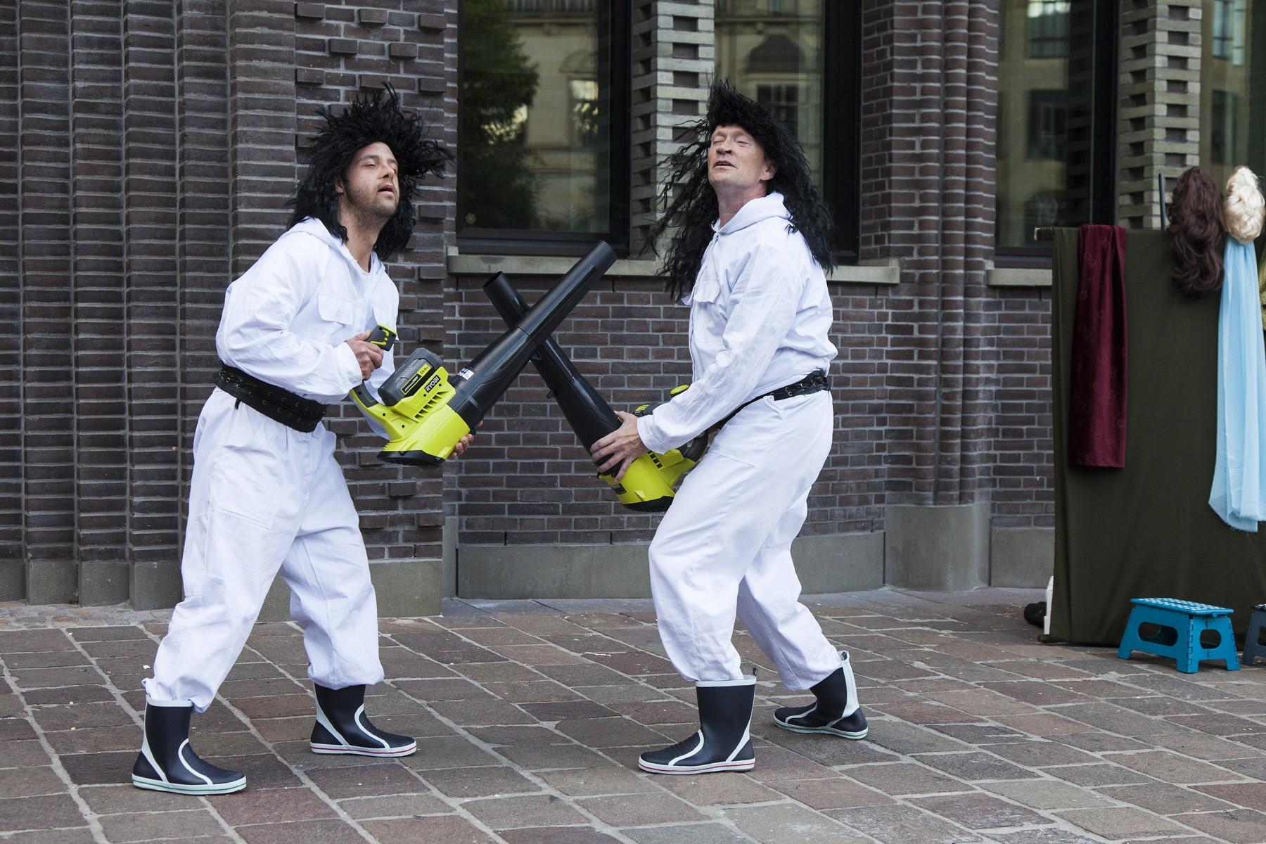 Zwei Männer mit Laubbläsern und Wind im Gesicht. Der Wind ist schön.