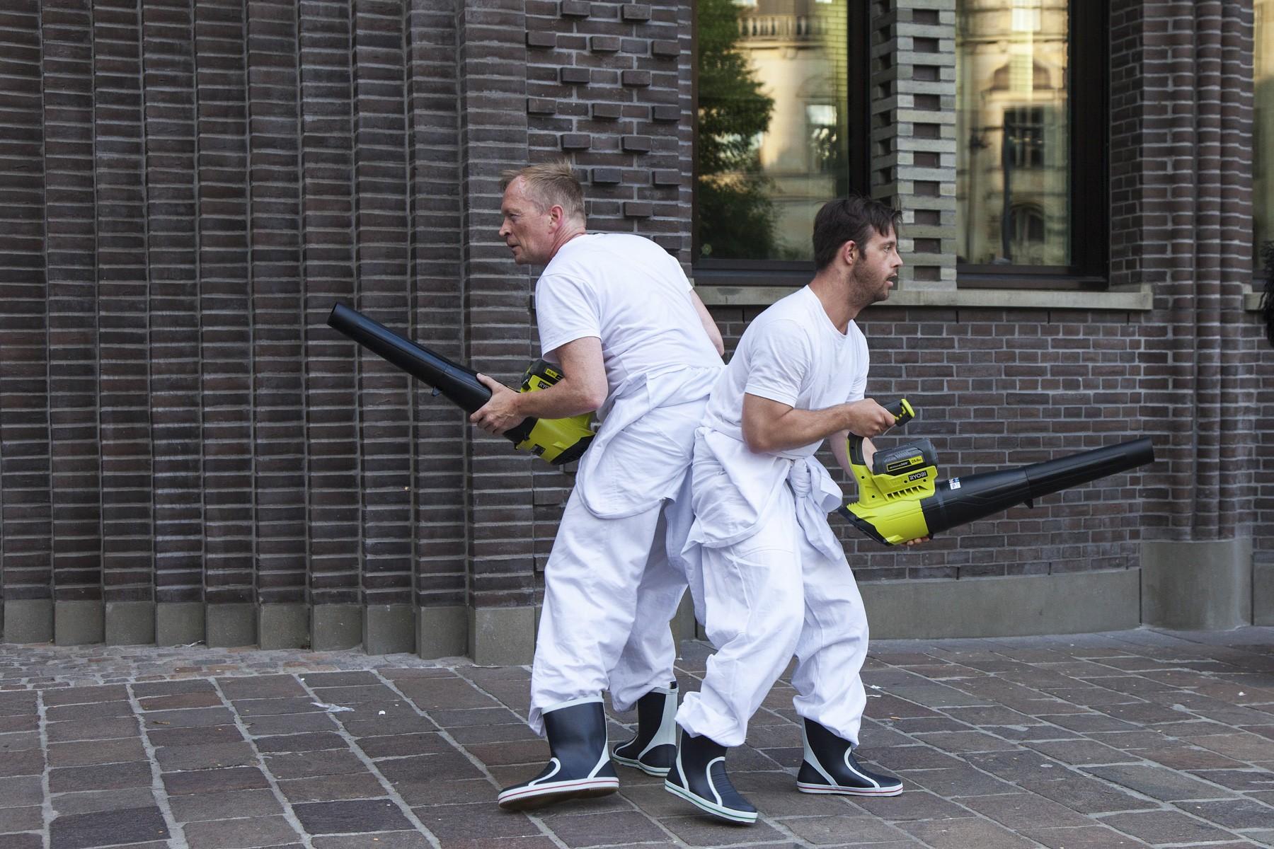 Zwei Männer Rücken an Rücken mit Laubbläsern. Jetzt komme ich!