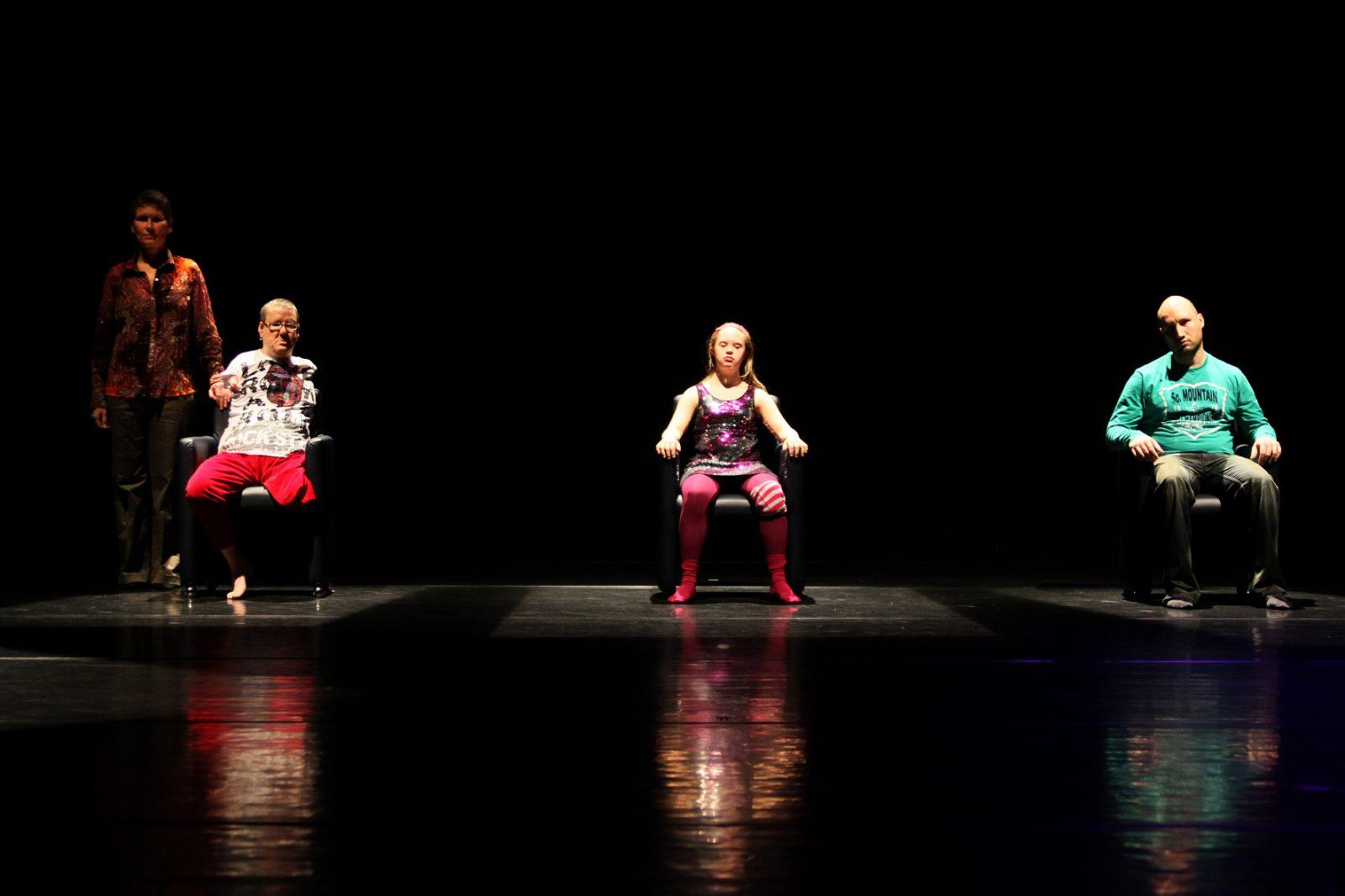 Drei TänzerInnen sitzen in Stühlen