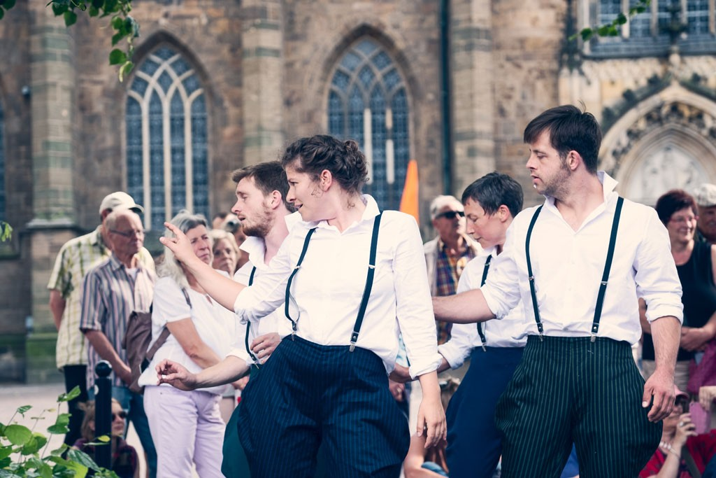 eine Gruppe von TänzerInnen hebt den rechten Arm