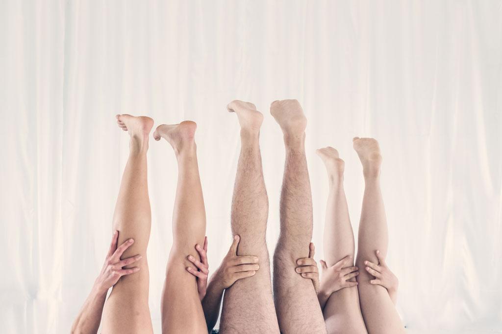 drei Paar Beine mit Händen in den Kniekehlen